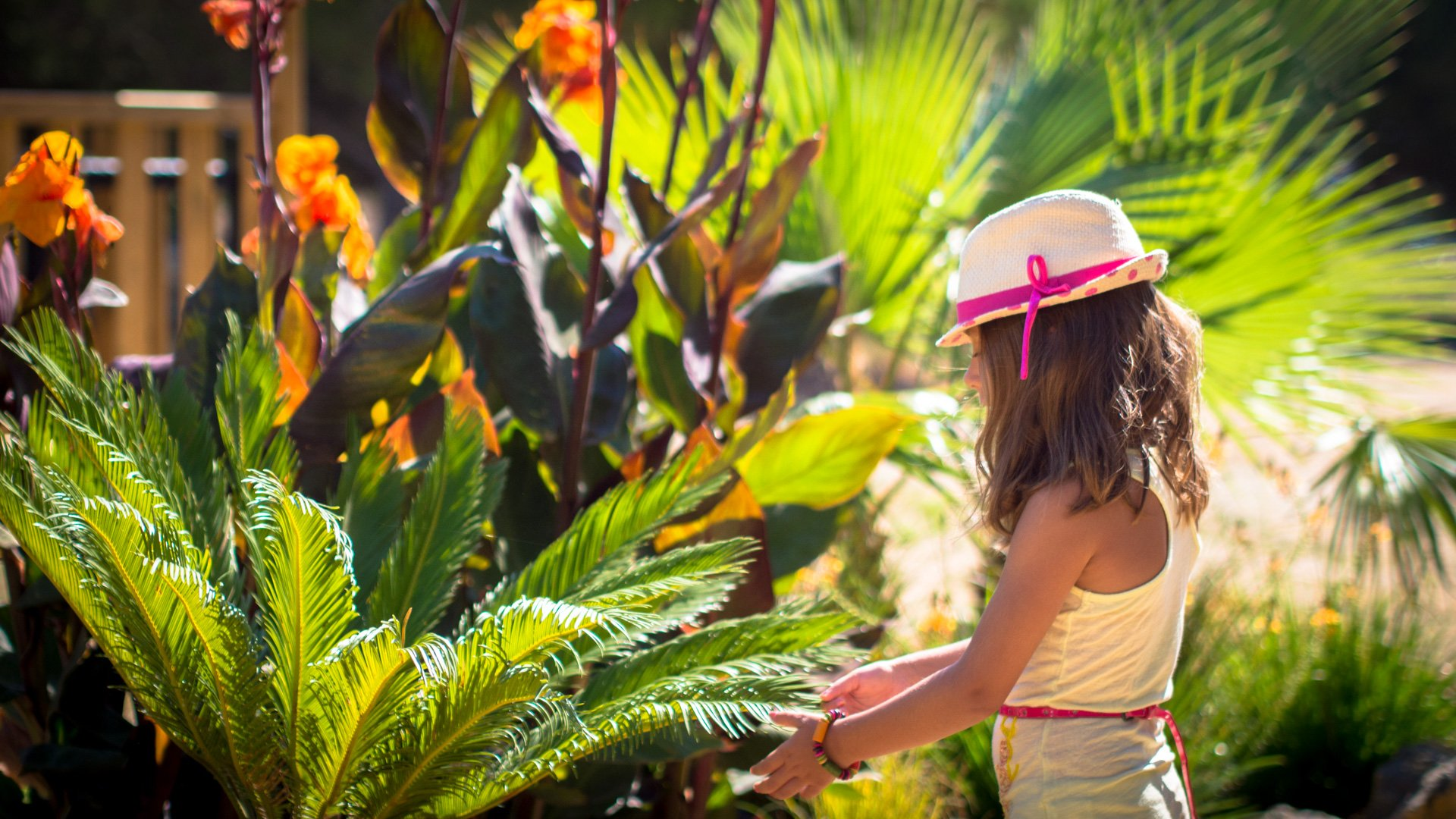 Une petite fille devant les fleurs et plantes du camping Le Bellevue valras